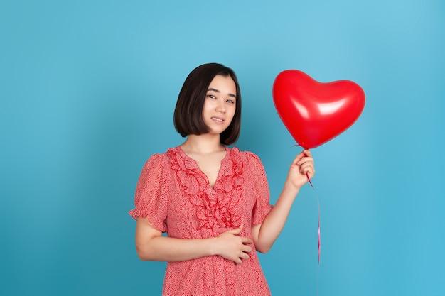 赤いドレスと黒髪のクローズアップの若いアジアの女性は、飛んでいる赤いハート型の風船を持っています