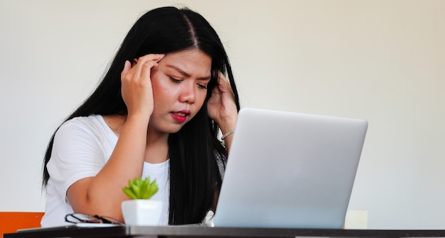 ノートパソコンの机、千年の深刻な燃え尽き概念で働く仕事で若いアジア女性ストレスを閉じる