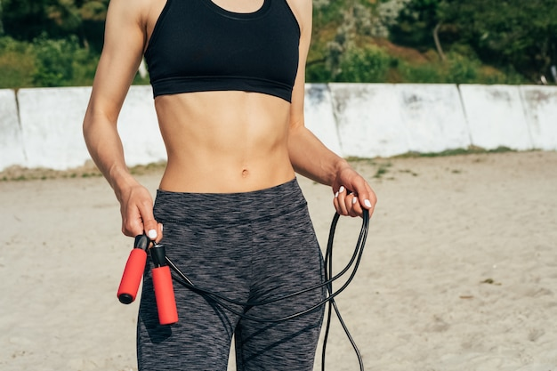 Close-up of a young athletic woman in sportswear holding a red skipping rope on the beach
