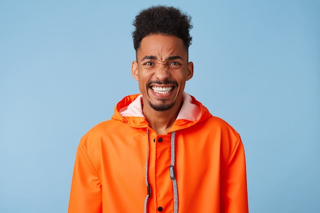 Close up of young attractive african american dark skinned boy wears in orange rain coat, feels very happy and crazy, smiles broadly stands.