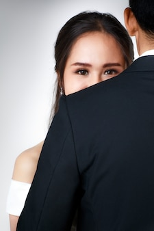 Close up of young attractive asian woman's eyes and upper face behind man's back hugging man. concept for pre wedding photography.