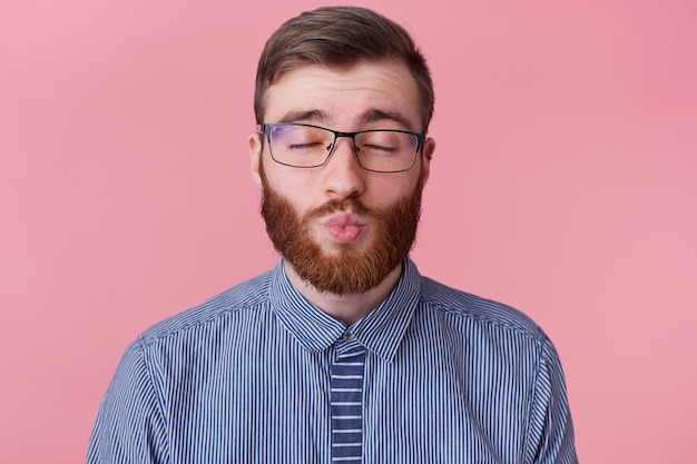 Close up of young attractive bearded man in a striped shirt with glasses, covering his eyes dreams of his beloved girl, sends her a kiss, isolated over pink background.
