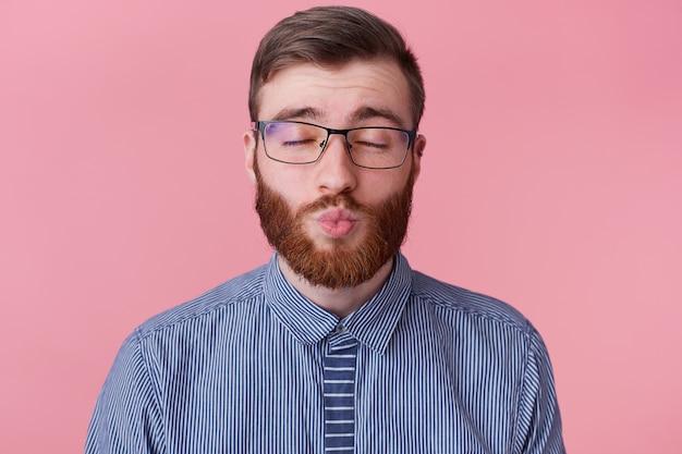 Primo piano di giovane uomo barbuto attraente in una camicia a righe con gli occhiali, che copre i suoi occhi sogni della sua amata ragazza, le manda un bacio, isolato su sfondo rosa.