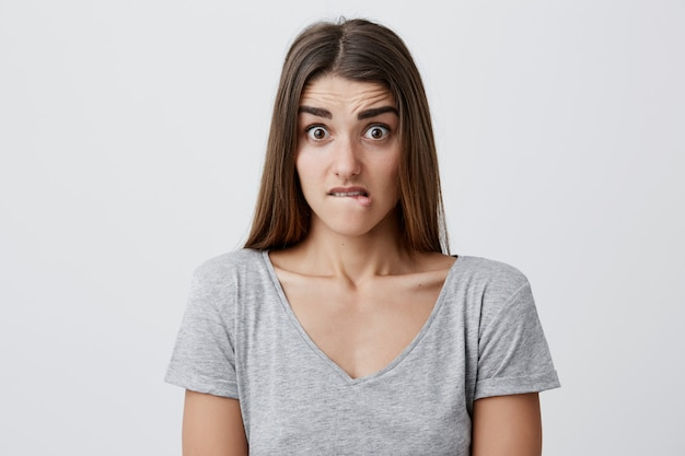 Close up of young attractive caucasian female student with long dark hair in gray t shirt looking  with shocked and scared expression, bitting lips