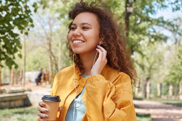 Chiuda in su della giovane ragazza riccia dalla pelle scura attraente che sorride ampiamente, indossa una giacca gialla, tiene una tazza di caffè, cammina nel parco, ascolta la musica e si gode il tempo.