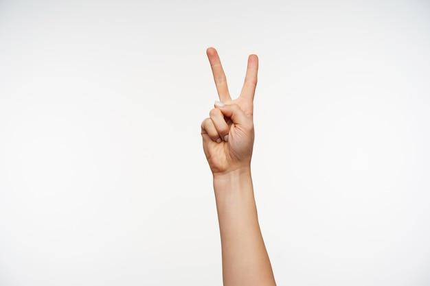 Primo piano sulla mano della giovane femmina attraente mantenendo due dita sollevate