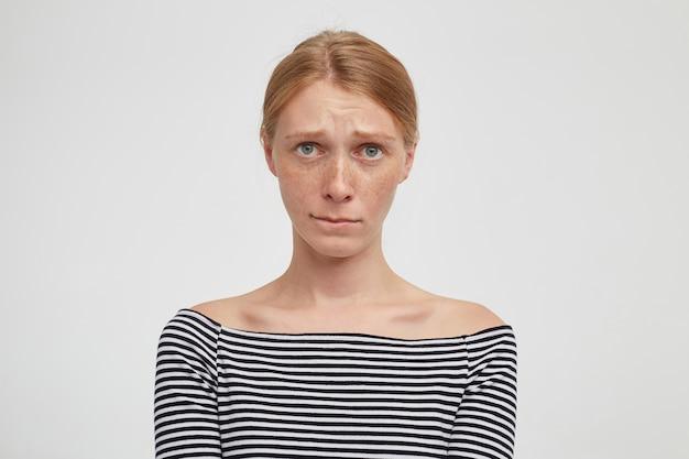 Primo piano sulla giovane femmina attraente rossa con acconciatura casual isolato