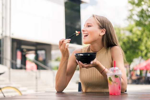 Close up of young attractive woman eating salad at street cafe