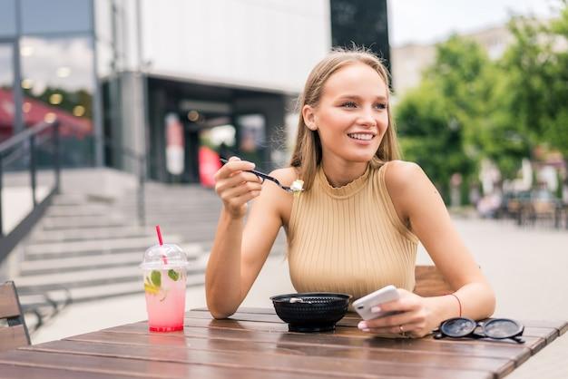 Primo piano di una giovane donna attraente che mangia insalata al caffè di strada?