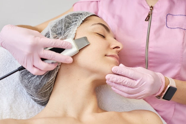 Close up of young attractive woman getting ultrasonic facial skin cleansing treatment by professional cosmetologist. adorable female wants to improve her face, needs refreshment. cosmetology concept.