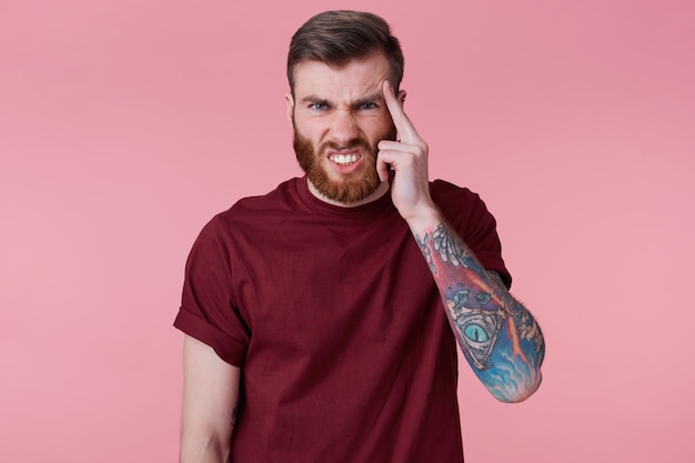 Close up of young bearded guy tattooed hand, with a finger at the temple like feels pin or forgot something important, writhing in pain isolated over pink background.