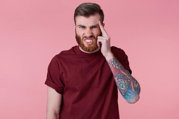 Primo piano del giovane ragazzo barbuto tatuato mano, con un dito alla tempia come si sente appuntare o dimenticato qualcosa di importante, contorcendosi nel dolore isolato su sfondo rosa.