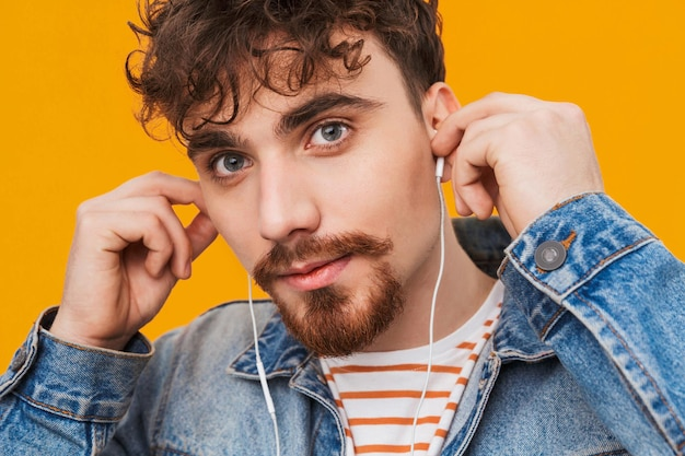 Close up of a young bearded man casually dressed listening to music with earphones isolated