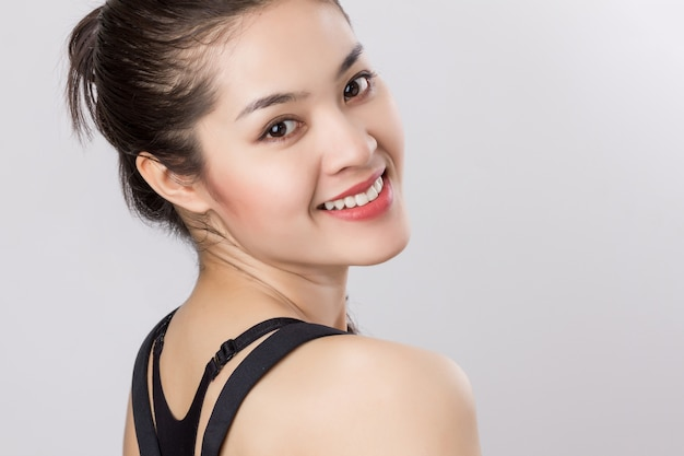 Close up young beautiful healthy asian woman with happy smiley face.
