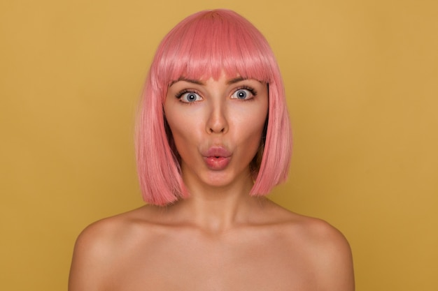 Close-up of young beautiful pink haired female with short trendy haircut rounding her blue eyes while looking surprisedly at camera, pouting her lips while posing over mustard background