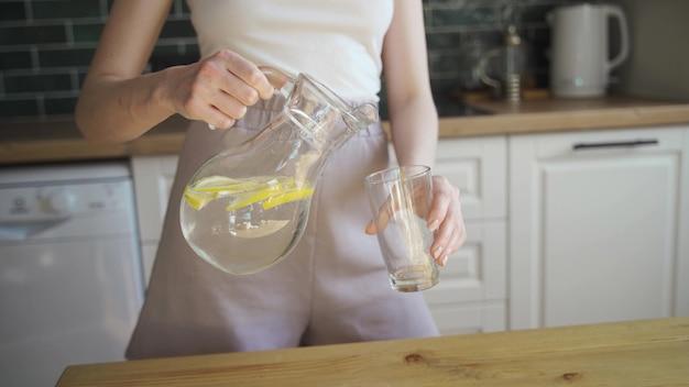 レモンとミントのデトックス水を飲むクローズアップの若い美しい女性。健康的な食事、美しい笑う女性の肖像画。スローモーションビデオ。