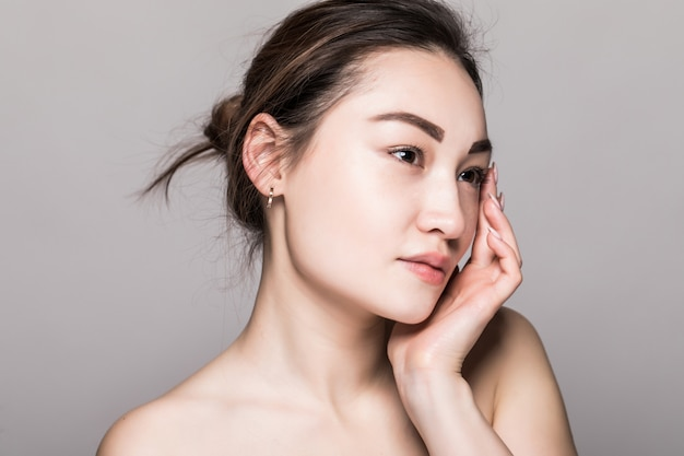 Close up young beautiful woman face isolated on gray wall
