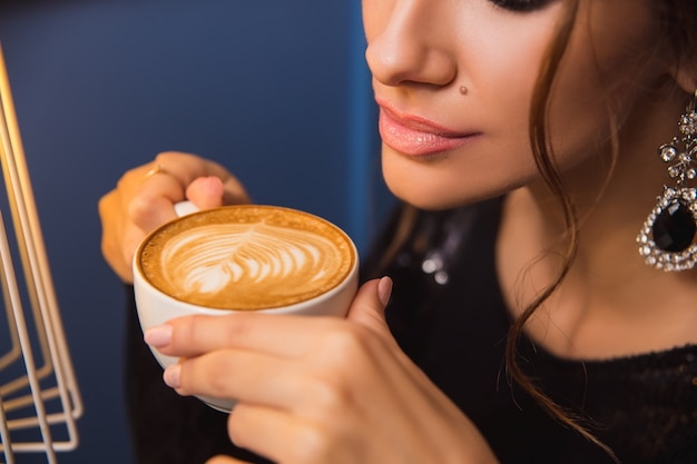 Close up of young beautiful woman hands holding hot cup of cappuccino