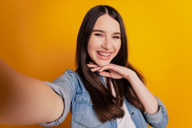 Close-up of young beautiful woman make selfie hand chin look camera on yellow wall