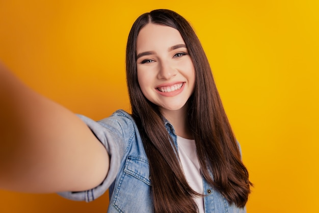 Close-up of young beautiful woman making selfie on yellow background