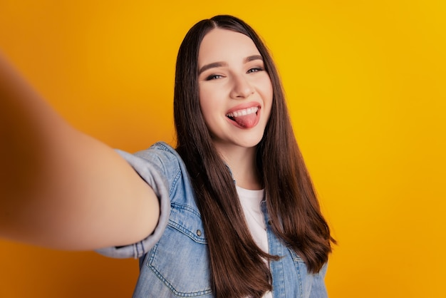 Close-up of young beautiful woman shoot selfie show tongue on yellow wall