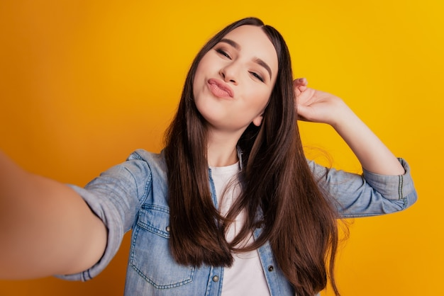 Close-up of young beautiful woman taking selfie send air kiss posing on yellow background