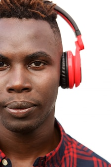 Close up young black guy listening to music with headphones