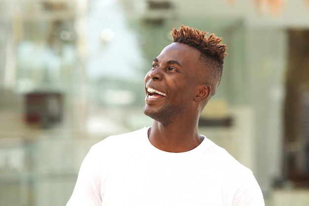 Close up young black man looking away and laughing