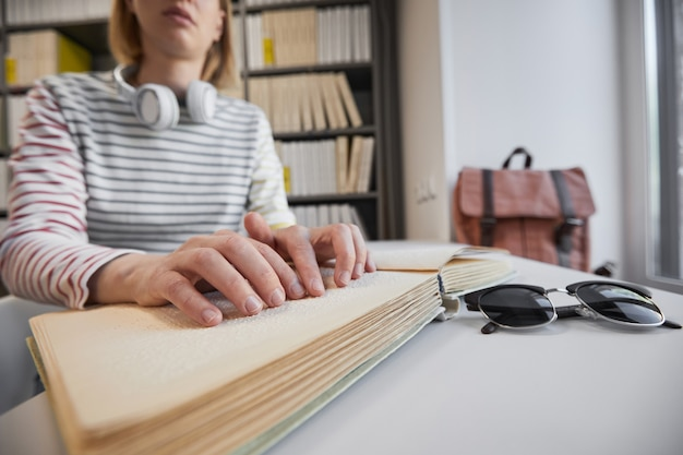 Close up of young blind woman reading braille book in college library copy space