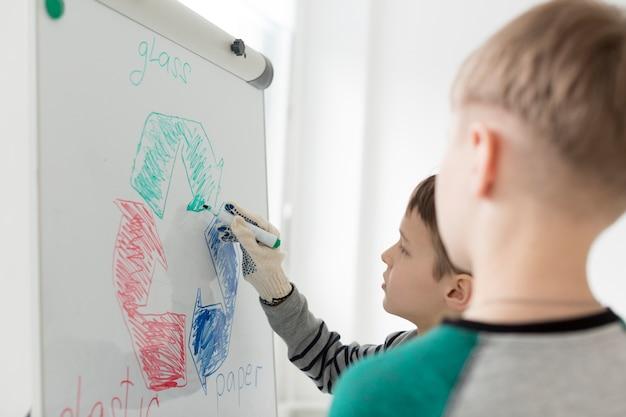 ホワイトボードにリサイクルサインを描くクローズアップの若い男の子