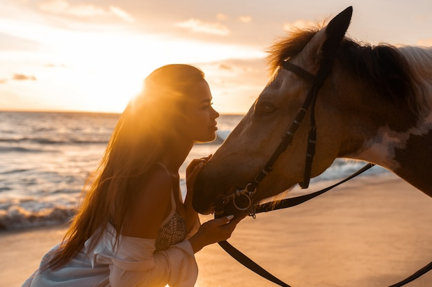 Close up: young brunette beauty having fun with horse on the beach. sunset