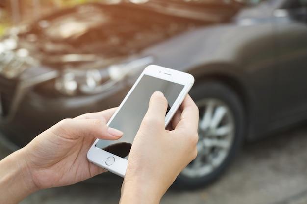 모바일 스마트 전화를 사용하여 젊은 비즈니스 맨 손을 닫습니다. 자동차 정비사가 도움을 요청합니다.