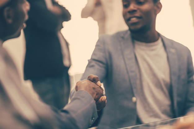 Close up. young business partners shaking hands. the concept of cooperation