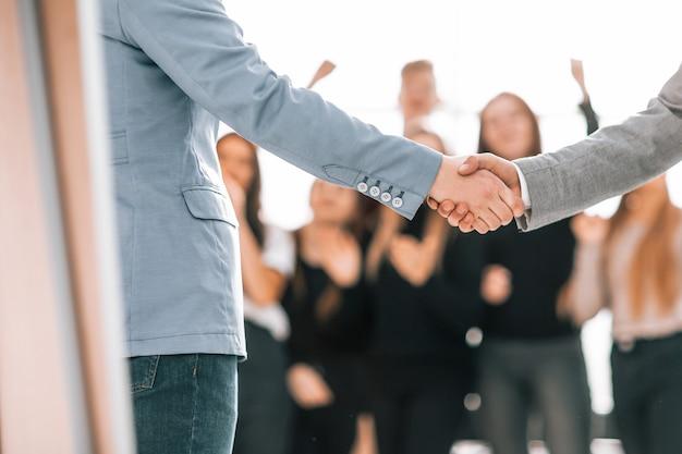 Крупным планом молодые деловые партнеры, пожимая руки
