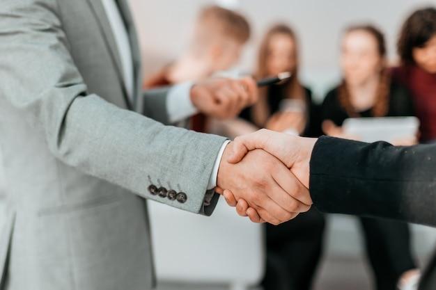 Крупным планом молодые деловые люди, пожимая друг другу руки