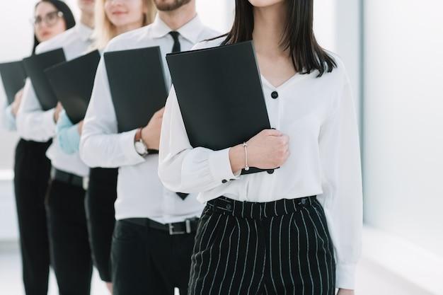 인터뷰를 위해 긴 줄에 서 있는 젊은 사업가들을 닫습니다. 경력 성장의 개념