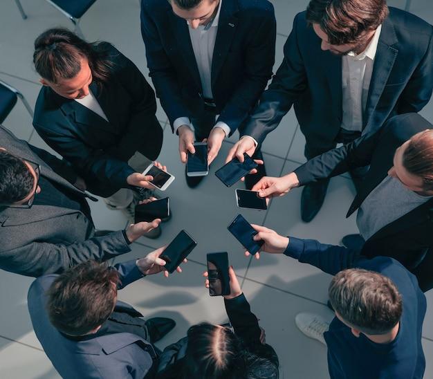 Закройте молодых деловых людей со смартфонами, стоя в кругу