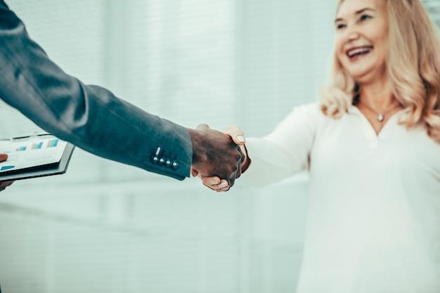 閉じる。握手で彼女のビジネスパートナーに会う若いビジネスウーマン。協力の概念