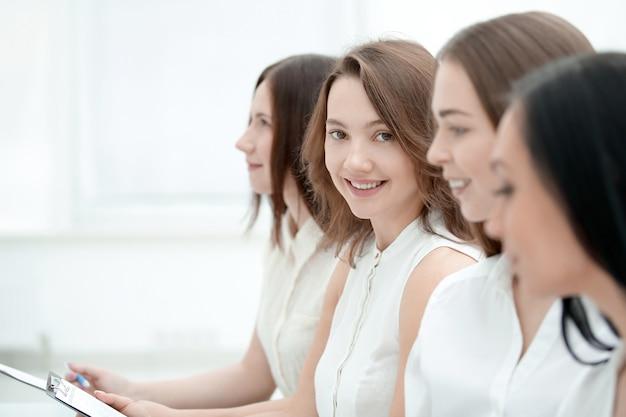 Крупным планом молодая деловая женщина на фоне коллег