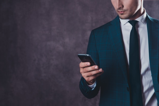 Close up of young businessman in black suit reading message