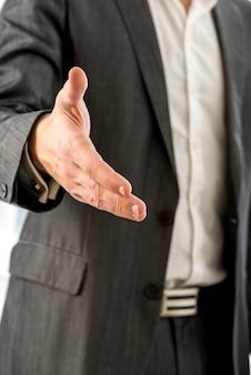 ハンドシェイクで手を提供している黒のスーツの青年実業家を閉じる