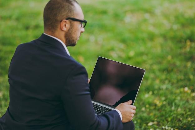 양복, 안경에 젊은 사업가를 닫습니다. 남자는 자연의 야외 녹색 잔디에 도시 공원에서 노트북 pc 컴퓨터에서 작업, 부드러운 pouf에 앉아. 모바일 오피스, 비즈니스 개념입니다. 뒷모습. 공간을 복사합니다.