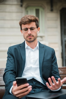 Close-up of young businessman talking on mobile phone with wireless earphone in his ears