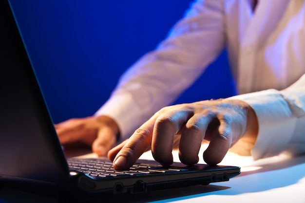 Close up of young businessman working on a laptop on dark background