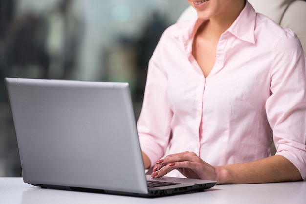 Close-up of a young businesswoman is using laptop at office.