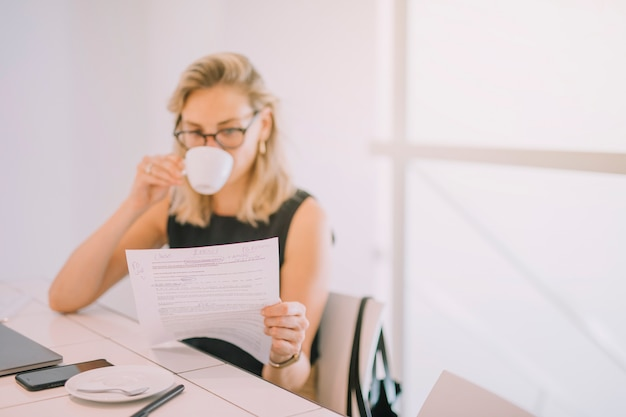 Close-up of young businesswoman reading the document while drinking the coffee