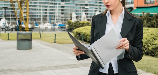Close-up of a young businesswoman reading folder at outdoors