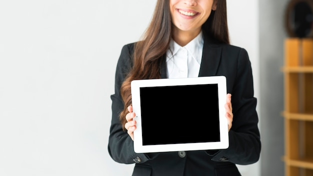 Close-up of a young businesswoman showing touch screen digital tablet