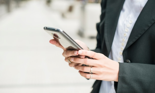 Close-up of a young businesswoman using smartphone
