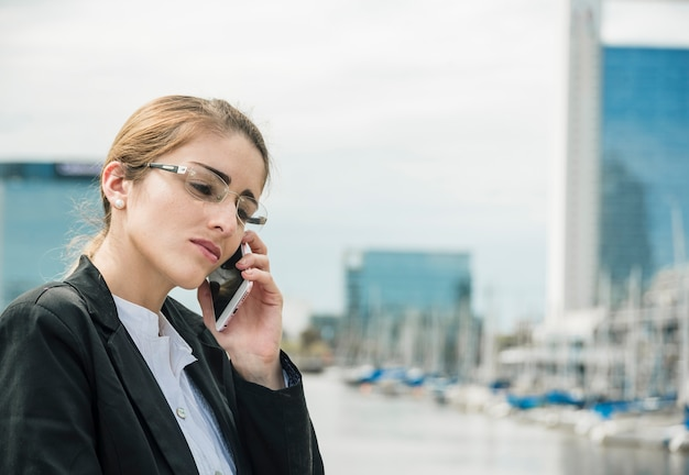 Close-up of a young businesswoman wearing eyeglasses talking on cell phone at outdoors